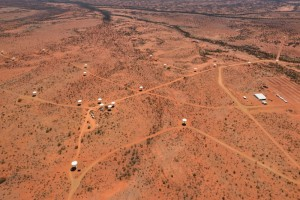 White dish shaped radio telescopes nad a large white building from the air on a red Australian desert backdrop.
