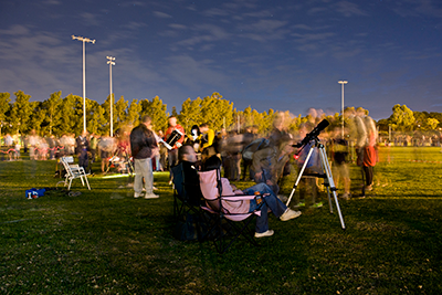 Visitors queue to view Saturn through a telescope at Astrofest 2012.