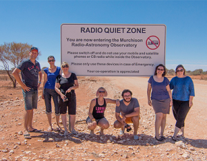 ICRAR Outreach staff and collaborators at the 'Radio Quiet' sign on the road near the MRO.