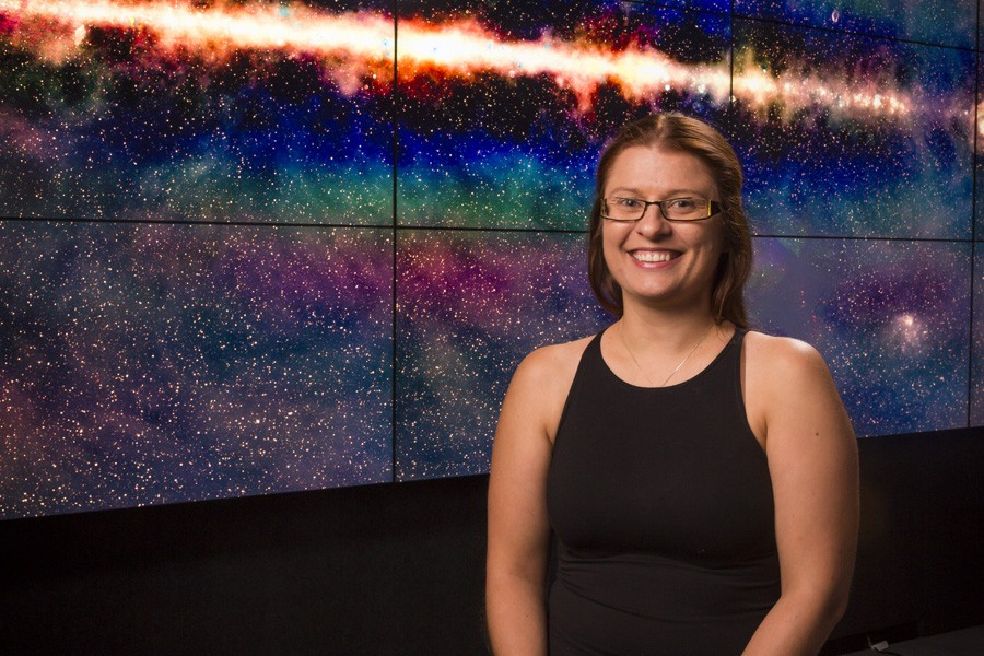 The lead author of the study, Dr Anna Kapinska, with the GLEAM radio sky image in the background. Credit: A.D.Kapinska.