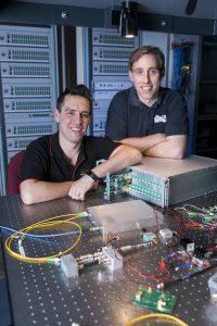 Sascha Schediwy and David Gozzard shown with an SKA-mid Transmitter Module and Sub-Rack enclosure. In the foreground is the Receiver Module to be installed at each antenna, and the background shows a mock-up of the entire 197-element system to be installed in the SKA's central processor building. Credit: ICRAR.