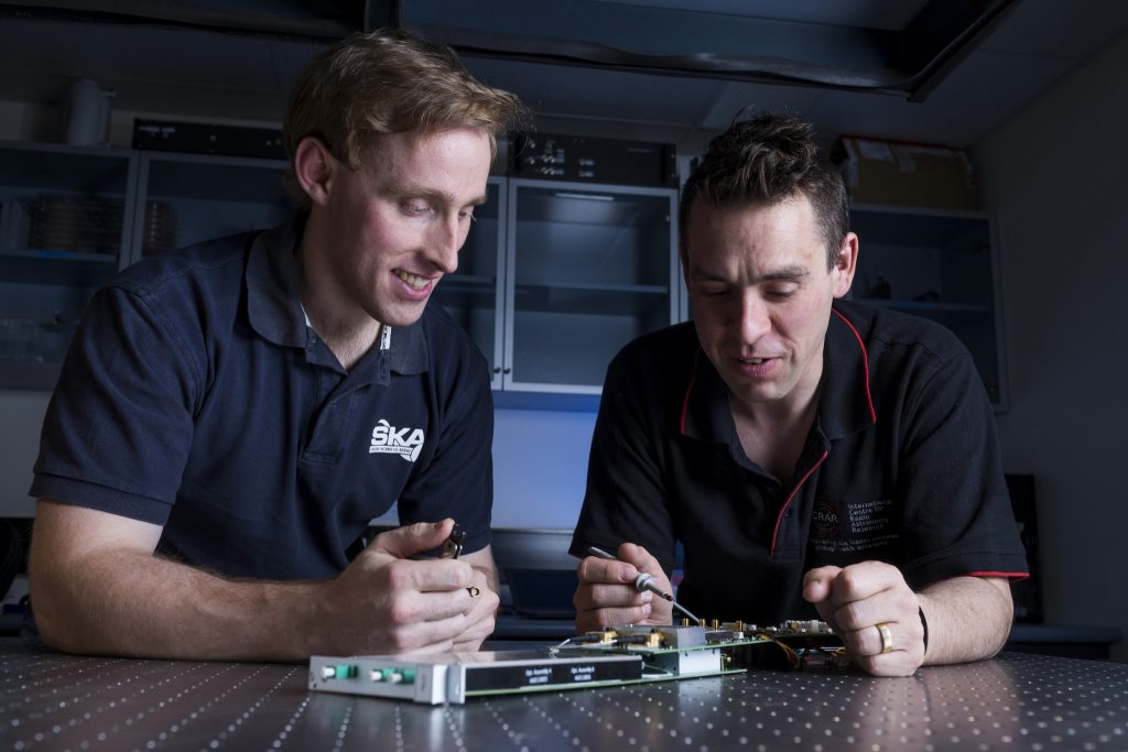 Sascha Schediwy and David Gozzard with components of their SKA-mid phase synchronisation system Transmitter Module. Credit: ICRAR.