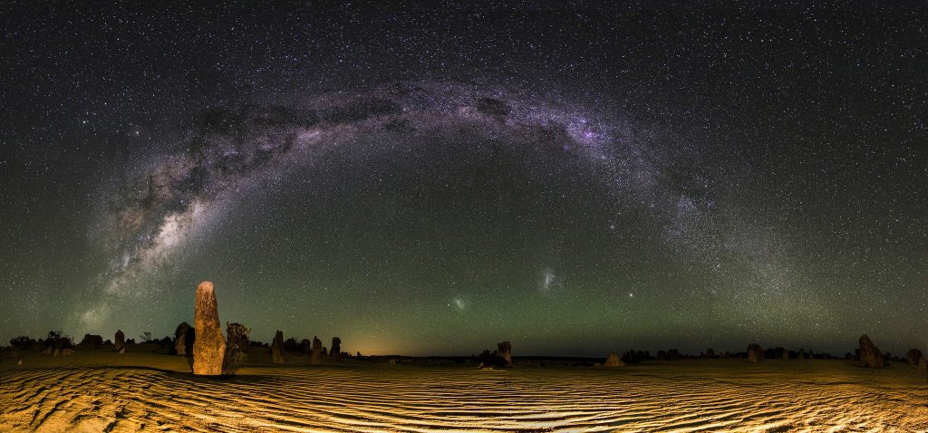 The Milky Way arching over the Large and Small Magellanic Clouds as viewed from the Pinnacles Desert in Western Australia. Credit: inefekt69 / Flickr.