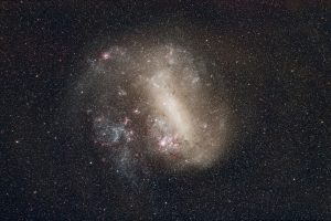 The Large Magellanic Cloud photographed using a small telephoto lens and a modified DSLR camera to highlight the red HII molecular clouds. Credit: Andrew Lockwood.