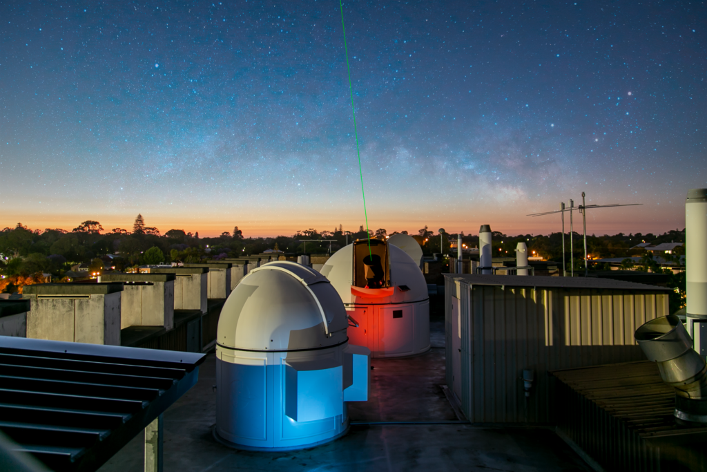 Rooftop observatories at dusk with a laser pointing to the sky.